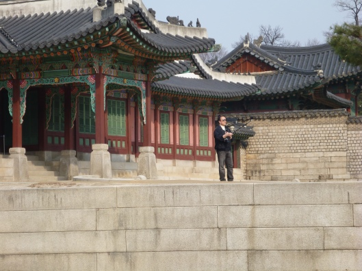 Korean man takes self-portrait with camera on stick in front of palace